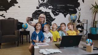 Happy female teacher with pupils are sitting of the desk and pose for selfie in geography class at elementary school. A young woman with children makes a selfie after classes in the geography