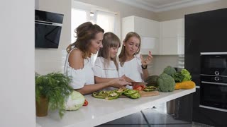 Happy mother and two her daughters is cooking vegetables for dinner at home kitchen. Food, healthy eating, family. The girls dressed in white dresses prepare vegetarian salad at home in the kitchen