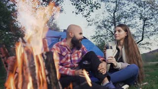 Happy young couple sitting by the fire in a tent town. Travelers have a rest with a cup of hot tea in the forest near a blue tent slow motion