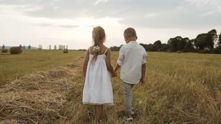 Little boy and girl after the rain took hands handsome running on the field slow motion