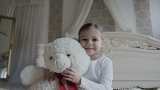 Little girl sits on a white carpet at the bed and hugs a soft, bear toy. Beautiful girl and her white soft toy bear slow motion