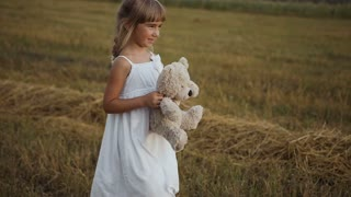 Little girl with beautiful dark eyes walks the field after the rain and is played by a toy bear slow motion