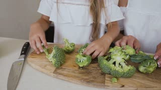 Little girl with her mother cutting fresh broccoli on carving board. Close-up shot hands of the female with slices broccoli preparing for food at home in the kitchen. Healthy lifestyle. Vegetables