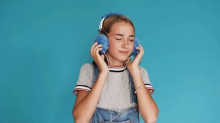 Lovely smiling girl is wearing big blue headphones listening to music inside of a studio. Hands on the headphones. Cute teenage girl listening to music through headphones on a blue background, slow