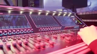 Male Dj hands playing set in night club party. Hands of Audio engineer working on a professional analog console, moving faders, mixing music slow motion