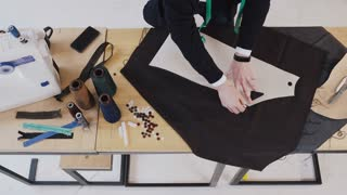 Male fashion designer working with sketches at studio. Male hands of tailor working in atelier and making pattern on material using paper of sketch, 4k