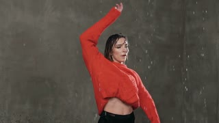 Modern dance. Wet girl dancer makes rotation around herself in the studio under the rain water, before studio light Girl dancer in red sweater perform contemporary dance under the drops of water rain