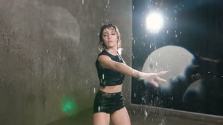 Modern dance wet young woman in the rain on stage. Wet dancer girl dancer circling around herself in the studio under the rain water, slow motion