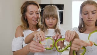 Mom teaches two kids daughters to cook at the kitchen table with raw green paprika at home in the kitchen. Mother teaching her daughters cutting vegetables in kitchen, slow motion