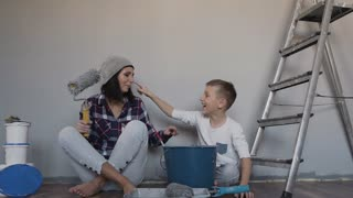 Mother and son finished repairing in the room they sits on the floor and painting each other with paint. A woman holds a roller in her hand. Happy day- finished repair slow motion