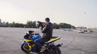 Motorcyclist on a sunset sits down on a motorcycle, wears a helmet and goes to the city slow motion
