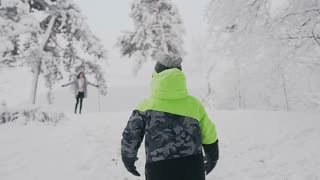 On a winter day in a snowy park, a little boy with open hands happily runs for a meeting with his mother. Happy mother and son. Christmas holidays slow motion