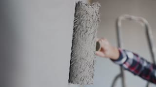 Painting out a bare wall with a paint roller with gray paint. Hand painting using paint roller. Painter girl at work, with roller painting wall, painter house concept 4k