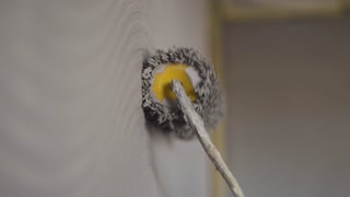 Painting out a bare wall with a paint roller with gray paint. Hand painting using paint roller. Painter girl at work, with roller painting wall, painter house concept slow motion