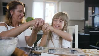 Playful Mum and daughter are making mustache from dough when baking biscuits together in the kitchen at home. Mom with her little girl have fun preparing dough for baking cookies, slow motion