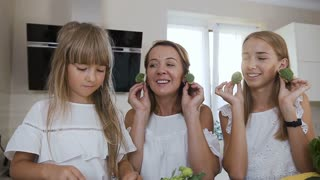 Portrait. Funny, young and cheerful family, are playing with broccoli in the kitchen while cooking. Close-up. Attractive mom with two her daughters dressed in white clothes have fun with vegetables