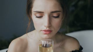 Portrait of a charming girl drinking champagne in the bathroom. Young beautiful woman drinks champagne relaxing in a hot bath, 4k