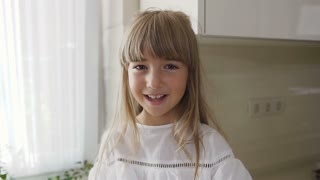 Portrait of a handsome little girl in white dress that eats tasty ripe tomatoes in the kitchen. Close-up. Cute kid eating tomatoes. Healthy and vegan food concept, slow motion