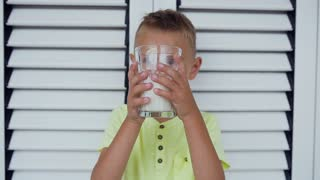 Portrait of a healthy kid boy with a glass of milk. A boy is drinking milk in about white door. Healthy eating. The right way of life. Little boy drinking milk, slow motion