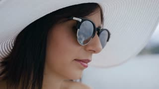 Portrait of a young woman with big hat and sunglasses enjoying sun and water. A pretty young brunette woman with big elegant hat and sunglasses, enjoy sunny day near blue ocean, vacation time. Close