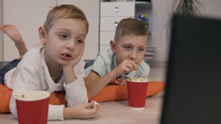 Portrait of beautiful children lying on the floor on orange pillows in the room eating delicious popcorn and looking funny cartoon slow motion
