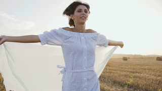 Portrait of the attractive brunette in long dress with light scarf running around the field of bales with raising hands on sunset at summer. Free woman, freedom health, slow motion