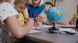 Primary school or kindergarten children drawing in the classroom with teacher helping. Portrait of a young caucasian teacher who teaches drawing their pupils during classes drawing, 4k