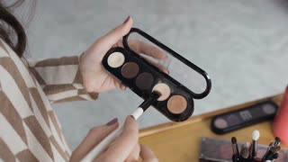Professional make-up shade. The girl holds the palette of eyeshadows in her hands and apply one of the shades to her brush. Makeup shadows in female hands, 4k