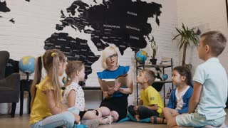 Pupils sit in circle on floor on the pillows as teacher reads to them interesting book in class at elementary school or kindergarten. A elementary or primary school a young female teacher reads a