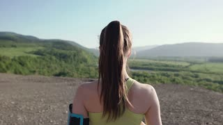 Rear view. Athlete girl jogging in mountains at sunset running from the camera and listen to music in headphone on a smartphone. Sportswoman listening to music during evening running training