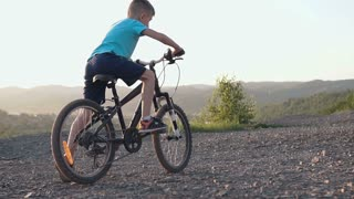Rear view of a boy who rides a black bike in a mountainous area. Child Cycling. Young boy riding a bike on the mountain road in suburbs in sunset at summer, slow motion