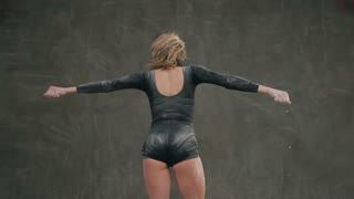 Rear View of a dancer girl who moving in cloud of white dust or powder on gray background at studio. Female ballet dancer in black body suit perform on stage in theater and using white powder or white