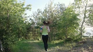 Rear view. Runner young woman running in park exercising outdoors fitness tracker wearable technology. Athlete girl jogging in park she running from the camera and listen to music in headphone on a