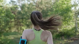 Rear view. Runner young woman running in park exercising outdoors fitness tracker wearable technology. Athletic girl training outdoor in the park, slow motion