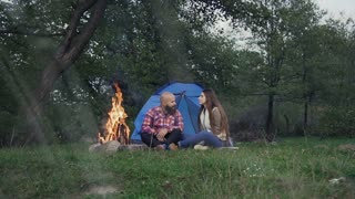 Rest on camping - A man who has a beard and woman with long hair is sitting at the burning fire in a tent town slow motion