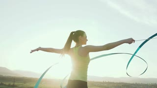 Rhythmic gymnastics: Girl in sport bodysuit perform gymnastics exercise with a blue ribbon on outdoor at sunset or sunrise. Gymnastic workout, slow motion