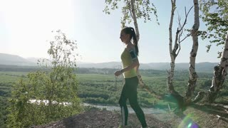 Running - girl runner jogging on forest path in mountains. Fit caucasian female sport fitness model athlete trail running training for cross country race. Athletic running girl at sunset in the