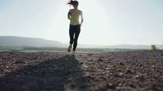 Running young woman trail running in mountain at sunset - female athlete runner sprinting fast. Sports girl running in sports shoes and sports wears in the mountains at sunset. Running in the