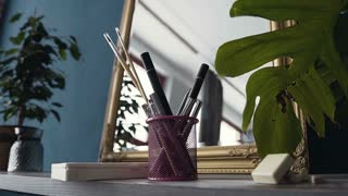 Set of brushes for make-up on table near mirror at room. Brush set for make-up on table in studio. Professional make-up tools. A set of brushes, lipsticks, shadows, carcass, slow motion