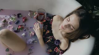 Sexy girl is relaxing in a warm milk bath with fragrant flower buds and drinking delicious red wine from the glass. Aromatherapy, body care. Healthy lifestyle concept,
