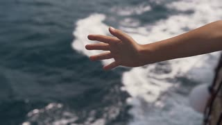 Ship in the open Adriatic Sea. The boy's hand in the air from the ship catches sea waves slow motion