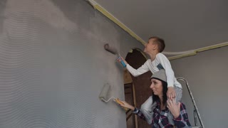 Sister with brother draw wallpapers on the wall in gray color roller in their room. Repair in the apartment slow motion