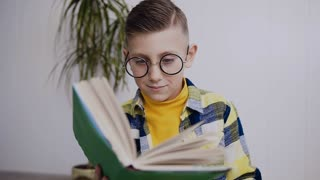 Six-seven year old boy with adult glasses read the book. Caucasian boy sits on the floor read the textbook has drinks drink with red cup. The little boy in glasses read the interesting book, in white
