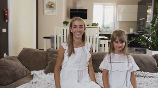 Slow motion footage of happy two teens sisters falling on bed at hotel room. Beautiful, happy girls in white dresses sitting on the bed looking at the camera and falling back in bed at home, slow
