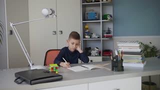 Small beautiful boy studying or doing homework, schoolboy studying with notebook and books on table. Cute beautiful pupil learning his lessons at home slow motion