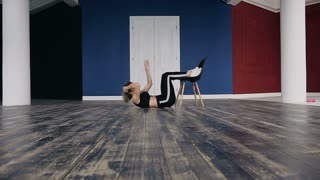 Sporty young woman doing press exercise at gym. A young and active woman in a sport suit strengthens the muscles of the press with a load of exercises, slow motion