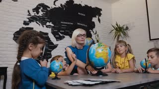 Teacher and kids discussing globe in geography classroom at primary school. Group of adorable caucasian students with teacher looks at the globe and study different countries, slow motion