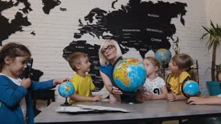 Teacher assisting school kids in reading globe in geography classroom at elementary school. An attractive teacher are educating of his pupils at elementary school and using a globe to teach them about