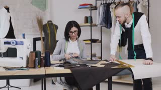 Team work of two tailor and dressmaker who are smile and working on sewing a new collection. The seamstress cuts pattern with scissors and the stylist follows the workflow, 4k