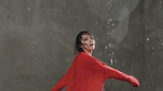The beautiful blonde girl in red sweater dancing under the drops of rain in the studio against the background of a gray wall. The dancer young woman performs a circular element in the dance, slow